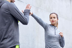 Женщина при тренер разрабатывая забастовку outdoors Стоковые Фотографии RF