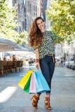 Женщина при хозяйственные сумки стоя на улице около Sagrada Familia Стоковое Изображение