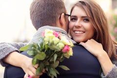 Женщина при цветки давая объятие к ее человеку Стоковые Фото
