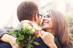 Женщина при цветки давая объятие к ее человеку Стоковое Изображение