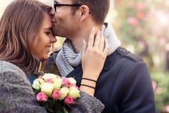 Женщина при цветки давая объятие к ее человеку Стоковое фото RF