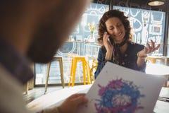 Женщина при человек говоря на телефоне в кафе Стоковая Фотография