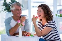 Женщина при человек есть еду Стоковые Изображения
