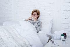 женщина при чихая нос дуя в ткани на кровати страдая холодные симптомы вируса гриппа имея медицины tablets пилюльки Стоковое фото RF