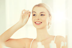 Женщина при щипчики tweezing бровь на ванной комнате стоковые изображения
