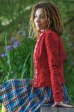 Женщина при dreadlocks сидя на стенде Стоковое Изображение