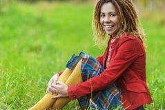 Женщина при dreadlocks сидя на траве Стоковое Изображение RF