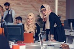 Женщина 2 при hijab работая на компьтер-книжке в офисе Стоковое Фото