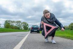 Женщина пробует построить ее предупреждающий треугольник стоковое изображение rf