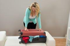 Женщина пробуя закрыть чемодан Стоковые Фотографии RF