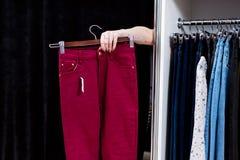 Женщина пробуя на брюках в магазине одежды достигая вне руку от примерочной держа брюки Стоковое фото RF