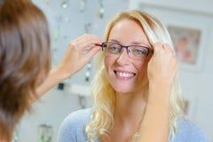 Женщина пробуя на стеклах в оптически магазине стоковые фотографии rf