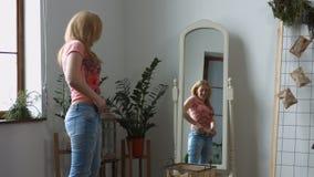 Женщина пробуя сжимать в старую пару джинсов сток-видео