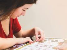 Женщина пробуя соответствовать частям игры мозаики стоковые изображения rf