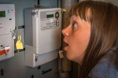 Женщина проверяет метр электричества - дорогое электричество conc стоковое фото