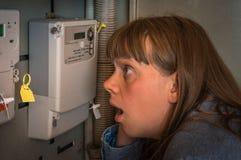 Женщина проверяет метр электричества - дорогое электричество conc стоковые изображения rf