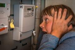 Женщина проверяет метр электричества - дорогое электричество conc стоковая фотография