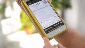 Женщина проверяет цену Bitcoin, баланс бумажника на экране smartphone мобильного телефона, ваша собственная концепция банка сток-видео