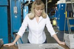 Женщина проверяя газету в фабрике стоковые изображения