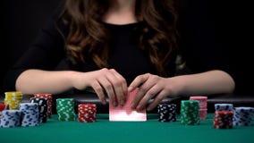 Женщина проверяя ее комбинацию карт в игре в покер на казино, играя в азартные игры наркомании стоковые изображения