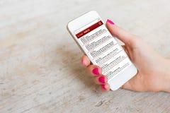 Женщина проверяя ее электронную почту на мобильном телефоне Стоковые Фото