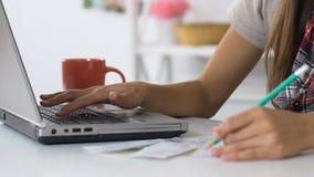 Женщина проверяя количество для общих назначений и арендных плат на счетах и оплачивать онлайн акции видеоматериалы