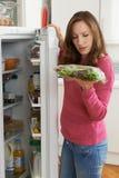 Женщина проверяя надувательство к дата на сумке салата в холодильнике стоковые фото