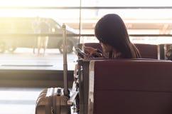 Женщина проверяя номер рейса на мобильном телефоне в авиапорте Стоковые Фото