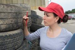 Женщина проверяя покрышки автомобиля Стоковые Фото