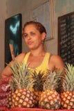 Женщина продавая ананасы стоковые изображения