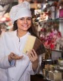 Женщина продавая шоколады и кондитерскаю Стоковое Фото