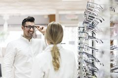 Женщина продавая eyeglasses к человеку клиента в магазине стекел Стоковая Фотография RF