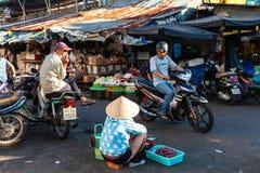 Женщина продает высушенных рыб на уличном рынке стоковое фото