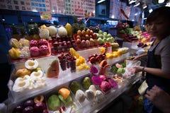 Женщина продает свежие фрукты на ее стойле на местном рынке ночи стоковое изображение