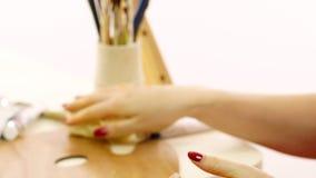 Женщина пропитывает палитру для красок масла Художник обтирает руки от масла Белая предпосылка Поднимающее вверх художника близко видеоматериал