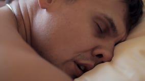 Женщина просыпает вверх и говорит к уснувшему мышечному парню в кровати, рано утром сток-видео