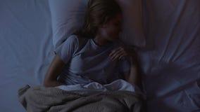 Женщина просыпая вверх из-за спазма в ее животе и принимая анальгетиков, взгляд сверху сток-видео