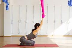 Женщина протягивает назад держать руки на розовом silk гамаке Стоковые Фотографии RF