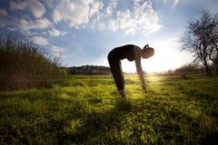 Женщина протягивая вне на поле стоковое фото