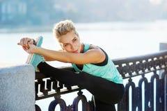 женщина протягивая ее ногу перед jogging утра Стоковые Фото