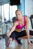 Женщина протягивая и нагревая для ее тренировки на спортзале Стоковое фото RF