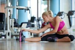 Женщина протягивая и нагревая для ее тренировки на спортзале Стоковая Фотография