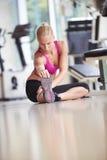 Женщина протягивая и нагревая для ее тренировки на спортзале Стоковое Изображение