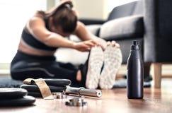 Женщина протягивая мышцы перед тренировкой разминки и веса спортзала в домашней живущей комнате Женский спортсмен фитнеса делая п стоковые фотографии rf