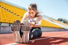 Женщина протягивая на поле на стадионе Стоковые Изображения