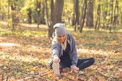 Женщина протягивая перед бежать в лесе стоковые фотографии rf