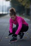 Женщина протягивая перед jogging утра Стоковая Фотография RF