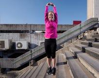 Женщина протягивая перед jogging утра Стоковое Изображение