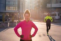 Женщина протягивая перед jogging утра Стоковые Изображения