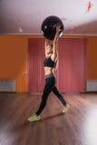 Женщина протягивая с накладными расходами шарика тренировки Стоковые Изображения